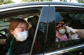 A young girl has her temperature checked as she arrives to watch a drive-in concert at the Gyeongbok Palace parking lot.