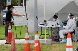 Health care workers take information from people in line at a walk-up COVID-19 testing site during the coronavirus pandemic,…