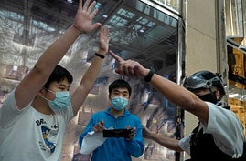 Protesters, center in blue shirt and left in white shirt, are detained by police officers as they gather at a shopping mall in…