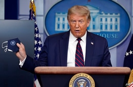 President Donald Trump holds a face mask as he speaks during a news conference at the White House, Tuesday, July 21, 2020, in…