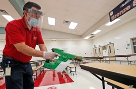 Wearing masks and face guards as protection against the spread of COVID-19, Garland Independent School District custodian Raul…