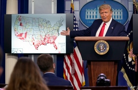 President Donald Trump gestures towards a graphic on the coronavirus outbreak as he speaks during a news conference