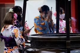 A restaurant employee wearing a protective face mask to help curb the spread of the coronavirus offer a joss sticks on a huge incense burner in the Asakusa district in Tokyo, July 27, 2020.