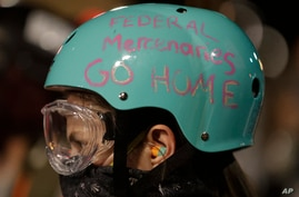 "A demonstrator's protective helmet reads ""Federal Mercenaries Go Home"" during a Black Lives Matter protest at the Mark O…"