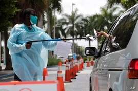 Healthcare worker Dante Hills, left, passes paperwork to a woman in a vehicle at a COVID-19 testing site outside of Marlins…
