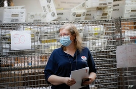 FILE- Cages loaded with ballots in United Postal Service bins rest behind a worker at a Board of Elections facility in New York…