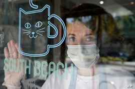 Celyta Jackson, owner of the Cat Cafe South Beach, looks out from her business during the coronavirus pandemic, July 29