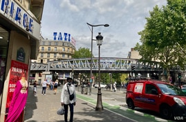 Tati's famous blue-and-pink logo soars over the Barbes Rouchechouart metro station in Paris. Lisa Bryant.jpg