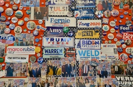 FILE - Campaign slogans, buttons, stickers and memorabilia of U.S. presidential candidates, past and present, some autographed, decorate a walls of the visitor center at the State House in Concord, New Hampshire, Feb. 3, 2020.