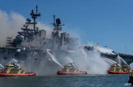 This U.S. Navy photo released July 13, 2020, shows sailors and federal firefighters battling a blaze onboard the amphibious assault ship USS Bonhomme Richard at Naval Base San Diego, California, July 12, 2020. (Christina Ross, U.S. Navy via AFP)