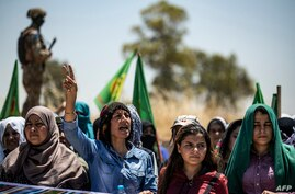 FILE - A Syrian Kurdish woman chants slogans during a rally in the countryside of the Hasakah province, Syria, June 27, 2020, to protest deadly Turkish offensives in northeastern areas of the country.