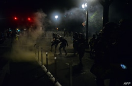 FILE - Police officers use tear gas during rally in Portland, Oregon, July 17, 2020. Rights activists and lawmakers expressed outrage over reports that federal agents in unmarked cars in the area were grabbing and detaining protesters off the streets.
