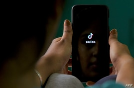 FILE - A mobile phone user opens the Chinese-owned video-sharing 'Tik Tok' app on a device in Bangalore, India, June 30, 2020.