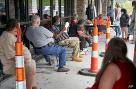 FILE - Job seekers exercise social distancing as they wait to be called into the Heartland Workforce Solutions office in Omaha, Nebraska, July 15, 2020.