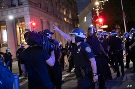 FILE - A police officer shouts at a video journalist in New York City, June 2, 2020, during demonstrations protesting the death in Minneapolis police custody of George Floyd.