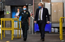 Britain's Prime Minister Boris Johnson, wearing a face mask, talks with paramedic Cindy Fu during a visit to the headquarters of the London Ambulance Service NHS Trust, July 13, 2020.