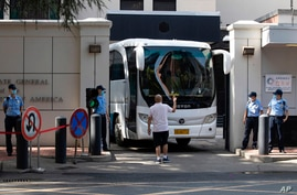 A bus is guided out of the United States Consulate in Chengdu in southwest China's Sichuan province, July 26, 2020.
