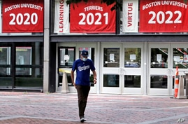 FILE - A student wearing a face mask exits Boston University's student union building, in Boston, Massachusetts, July 23, 2020. Dozens of U.S. colleges are announcing plans to test students for the coronavirus this fall, but their strategies vary widely.