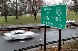 FILE - A sign welcomes motorists to New York, on the border with Connecticut, near Rye Brook, New York, March 29, 2020.