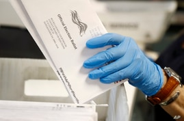 FILE - A worker processes mail-in ballots at the Bucks County Board of Elections office prior to the primary election in Doylestown, Pennsylvania, May 27, 2020.