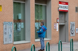 FILE  - A man looks at notices on the window of an unemployment office in Madrid, Spain, April 28, 2020.