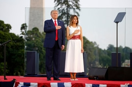 """President Donald Trump and first lady Melania Trump hold their hands over their hearts during a rendition of the national anthem as part of a """"Salute to America"""" event, the South Lawn of the White House, in Washington, July 4, 2020."""