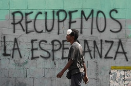 "FILE - A man with a misplaced face mask walks past graffiti on a wall that reads in Spanish ""Let's get hope back,"" in Caracas, Venezuela, March 29, 2020."