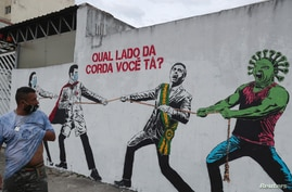 "FILE - A man passes graffiti depicting Brazilian President Jair Bolsonaro and a coronavirus representation engaged in a tug-of-war with health workers, in Sao Paulo, Brazil, June 10, 2020. The text in red reads: ""Which side are you on?"""