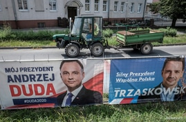 FILE - Election posters of incumbent Polish President Andrzej Duda, left, and Warsaw mayor and presidential candidate of the main Polish opposition party Civic Platform (PO) Rafal Trzaskowski hang on a fence in Leszno, Poland, July 6, 2020.