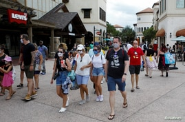 FILE - Disney Springs shoppers wear face masks and Disney-themed clothing while Walt Disney World conducts a phased reopening after coronavirus restrictions, in Lake Buena Vista, Florida, July 11, 2020.