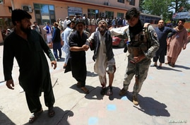 Men carry an injured person to a hospital after a blast during a funeral ceremony in Jalalabad, Afghanistan, May 12, 2020.