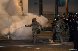A federal law enforcement officer uses tear gas during a protest over racial inequality in Portland, Oregon, July 17, 2020.