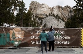 Visitors take a photos of the Mount Rushmore National Memorial in Keystone, South Dakota, April 16, 2020.