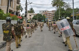 Police personnel patrol on a street in Bangalore on August 12, 2020, after violence broke out overnight in Devara Jevana Halli…