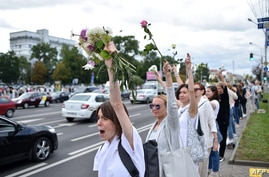 Women with flowers stand along a street as they protest against police violence during recent rallies of opposition supporters,…