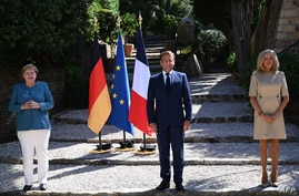 French president Emmanuel Macron (C) and his wife Brigitte Macron (R) welcomes German Chancellor Angela Merkel at Fort de…
