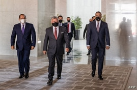 A handout picture released by the Jordanian Royal Palace on August 25, 2020, shows Jordanian King Abdullah II (C) arriving with…