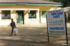 A sign outside the Higher Shariah Court in the northern Nigerian cityof Gusauthe in the state of Zamfara, demonstrates the…