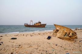 A decaying boat is seen docked off the port of Nouadhibou June 25, 2014. Mauritania's SNIM iron ore mining company aims to…