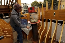 Scientist Eric Dimond of the San Francisco Eploratorium, cranks a desalination pump by hand to display the process of turning…