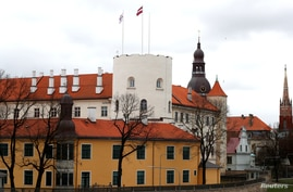 Latvian flag and presidential standard flutter over the Riga Castle, in Riga, Latvia April 9, 2019. REUTERS/Ints Kalnins