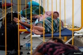 FILE PHOTO: FILE PHOTO: Migrant workers rest at a swab isolation facility as they wait for their test results at a dormitory,…