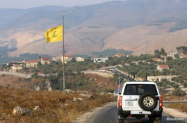 A UN peacekeepers (UNIFIL) vehicle drives past a Hezbollah flag in the southern Lebanese village of Khiam, near the border with…