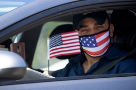 Palestinian Omar Abdalla waves a U.S. flag after being sworn-in as a newly naturalized United States citizens during a drive…