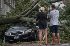 People look at a fallen tree on a car in the aftermath of Tropical Storm Isaias in the Rockaway area of Queens in New York City…