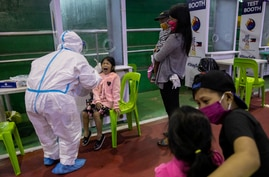 A child reacts after getting swabbed for a free coronavirus disease (COVID-19) test at a gymnasium in Navotas City, Metro…
