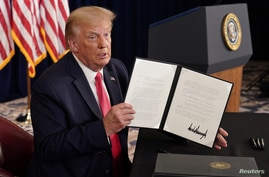 U.S. President Donald Trump shows signed executive orders for economic relief during a news conference amid the spread of the…