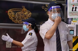 Security guards wearing face shields require people have their body temperature checked at an entrance of a shopping centre,…