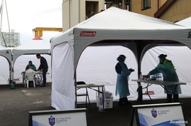 Medical workers and members of the public are seen at a pop-up testing centre for the coronavirus disease (COVID-19) in Sydney,…