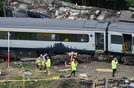Emergency services inspect the site, following the derailment of the ScotRail train which cost the lives of three people, near…